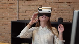 Young woman using vr glasses for watching the video in the modern office.