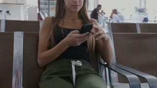 Young woman waiting for her flight at the International Airport.