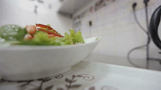 Waiter in a restaurant brings a delicious fresh salad dish to the table on a tray