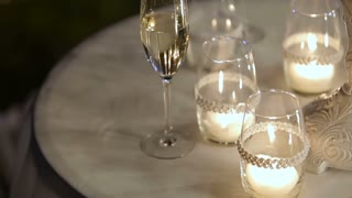 Wedding evening ceremony decor, table with Closeup candles and champagne glasses.