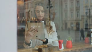 Woman using tablet computer touchscreen in cafe drinking coffee