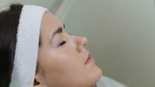 Woman with closed eyes getting photo rejuvenation procedure in a beauty salon.Cosmetician perfiming photo rejuvenation cosmetology procedure for a woman.Skin care. Young woman receiving facial beauty