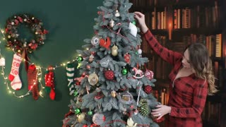 Young beautiful woman in red dress , putting toys on a Christmas tree.