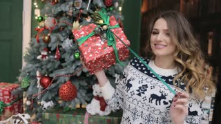 Young beautiful woman wearing warm sweater, enjoy her Christmas gifts near the Christmas tree.