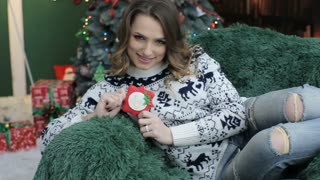 Young beautiful woman wearing warm sweater , sitting on a green chair with New Year BAKING near the Christmas tree.