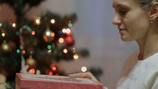 Young Beauty teen girl opens Christmas gift box with miracle. Christmas and New Year tree. Amazed Happy woman getting magic gift.