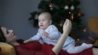 Young charming mother and her cute daughter playing at christmas tree at home
