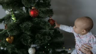 Young charming mother and her cute daughter playing with Christmas Decorating and New Year Tree