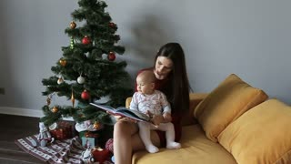 Young charming mother and her cute daughter sitting at christmas tree at home reading a book