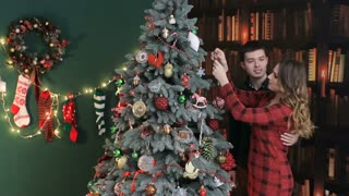 Young couple in love, putting toys on a Christmas tree.