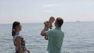 Young family playing with baby at sea coast