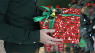 Young man gives a gift,present in a red and green colored box  for his girlfriend.Congratulate Happy New Year, Merry Christmas, Happy Valentine's Day, presents gifts