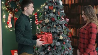 Young man gives a gift,present in a red colored box for his girlfriend. Congratulate Happy New Year, Merry Christmas, Happy Valentine's Day, presents gifts