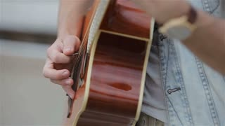 young man playing the acoustic guitar.Close up of a guitarist playing acoustic guitar. slow motion