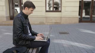 Young man using his laptop on a street bench and talking on the Smartphone