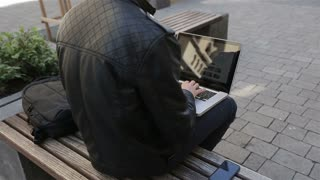 Young man using his laptop on a street bench.man typing on his laptop