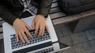 Young man using his laptop on a street bench.man typing on his laptop.View from top