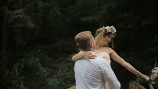Young romantic pair - pretty girl in light dress and handsome man turns a girl on a bridge in the forest