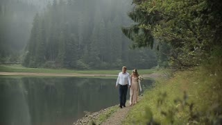 Young romantic pair - pretty girl in light dress and handsome man walking along the lake shore