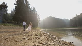 Young romantic pair - pretty girl in light dress and handsome man walking along the shore of the lake at sunset