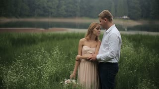 Young romantic pair - pretty girl in long light dress and handsome man hugging in the grass on the mountains background
