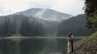 Young romantic pair - pretty girl in long light dress and handsome man hugging on the lake and mountains background