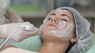 Young woman getting ultrasonic deep facial cleansing in cosmetology salon