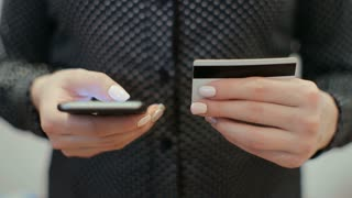 Young woman hands buying goods from the internet on her smartphone with her credit card.