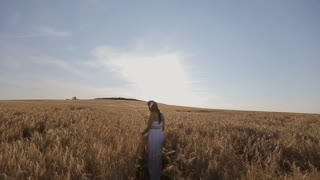 Young woman in white sun dress walking through grassy field at sunset.Slow motion