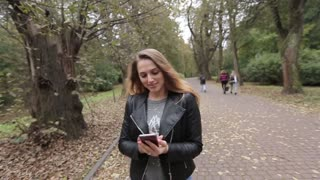 Young woman using smartphone during walk in city park