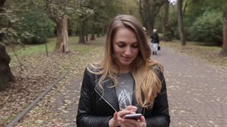 Young woman with smartphone walking in the park, steadicam shot