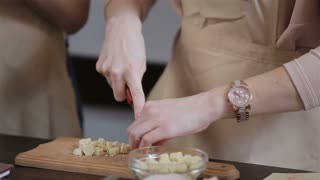young women cuts pieces of white chocolate.cupcake