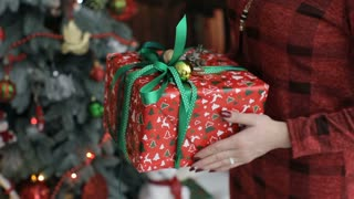 Young women gives a gift,present in a red and green colored box for his boyfriend. Congratulate Happy New Year, Merry Christmas, Happy Valentine's Day, presents gifts