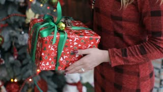 Young women gives a gift,present in a red and green colored box for his boyfriend.