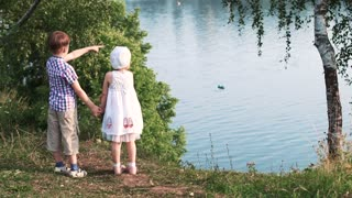 2 kids standing near the river outside