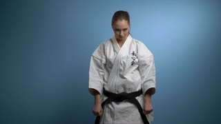 A girl in a karate pose isolated on blue