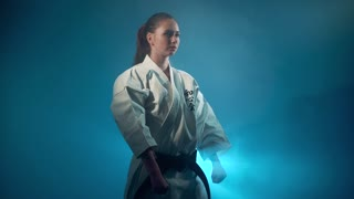 A woman in a karate pose isolated on blue