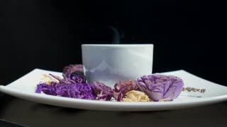 Adding sugar to cup of tea with flowers rotating