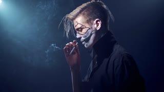 an Evil man with halloween makeup smoking