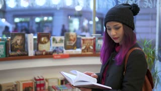 Asian girl reads book in supermarket
