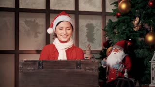asian woman in hat opening a chest with gifts
