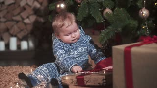 Baby boy under Christmas tree with gifts
