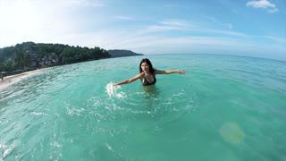 Beautiful bikini model splashing water in sea