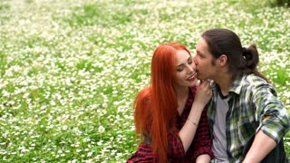 beautiful couple in love sitting in grass