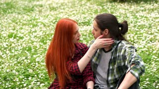 beautiful couple petting in spring grass