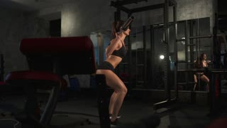 beautiful sporty sexy woman doing squat in gym
