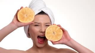 Beautiful woman holding orange slices in front of her face