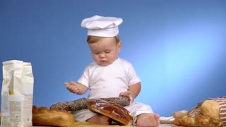 child among bread on blue wall in cook hat