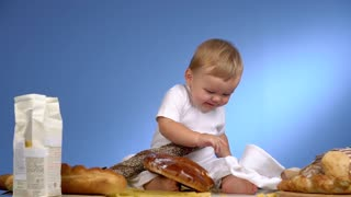 child playing with bread on blue wall