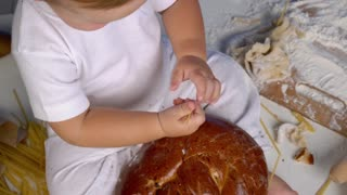 child playing with bread on white table
